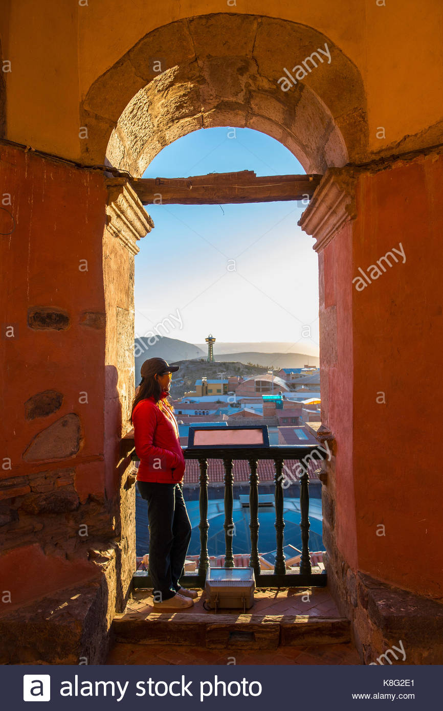 Female tourist looking over Potosi rooftops from archway, Bolivia - Stock Image