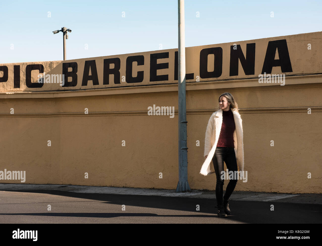 Female tourist strolling by wall with Barcelona in capital letters, Barcelona, Spain - Stock Image