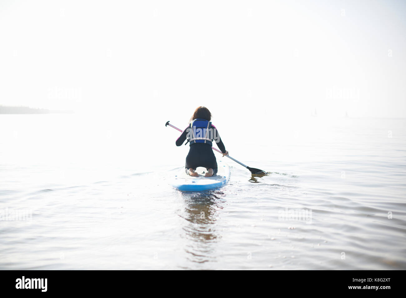 Rear view of female paddleboarder paddling out on misty sea - Stock Image