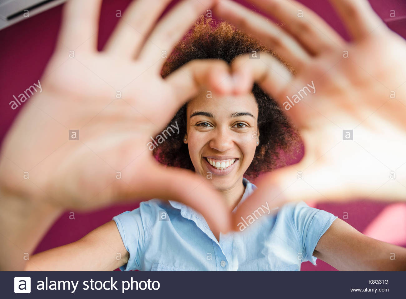 Portrait of young woman making heart shape with hands and fingers - Stock Image