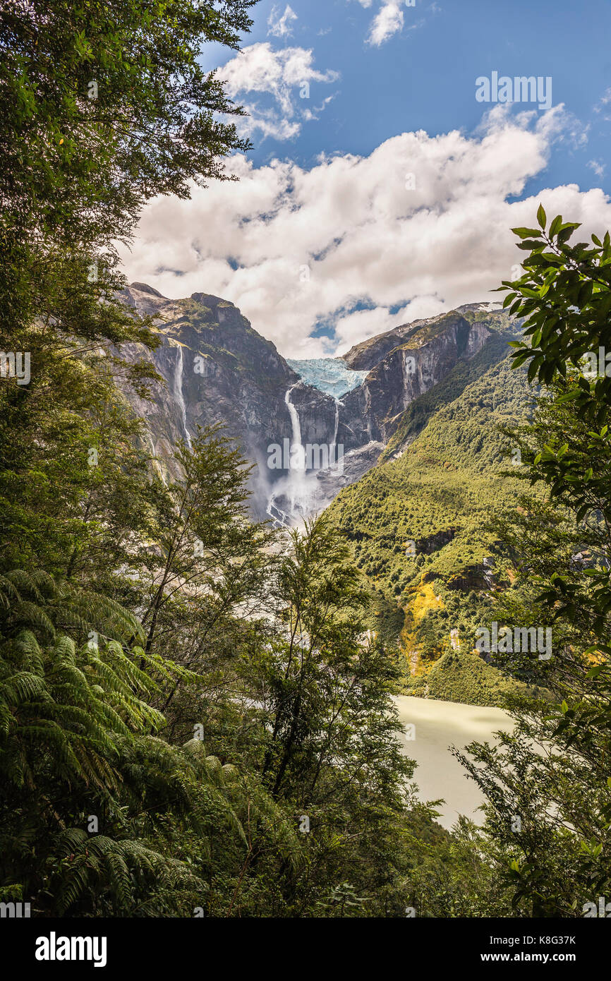 View of waterfall flowing from glacier at edge of  mountain rock face, Queulat National Park, Chile - Stock Image