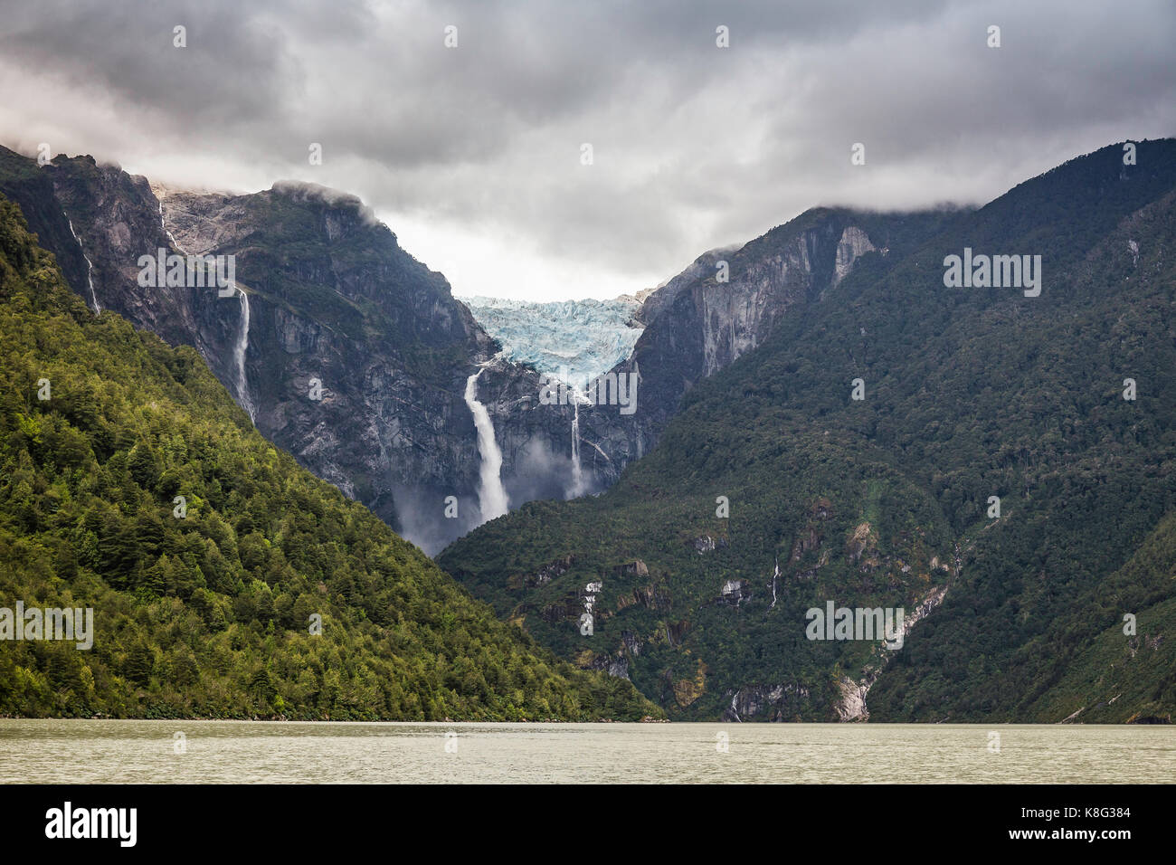 Waterfall flowing from glacier at edge of mountain rock face, Queulat National Park, Chile - Stock Image