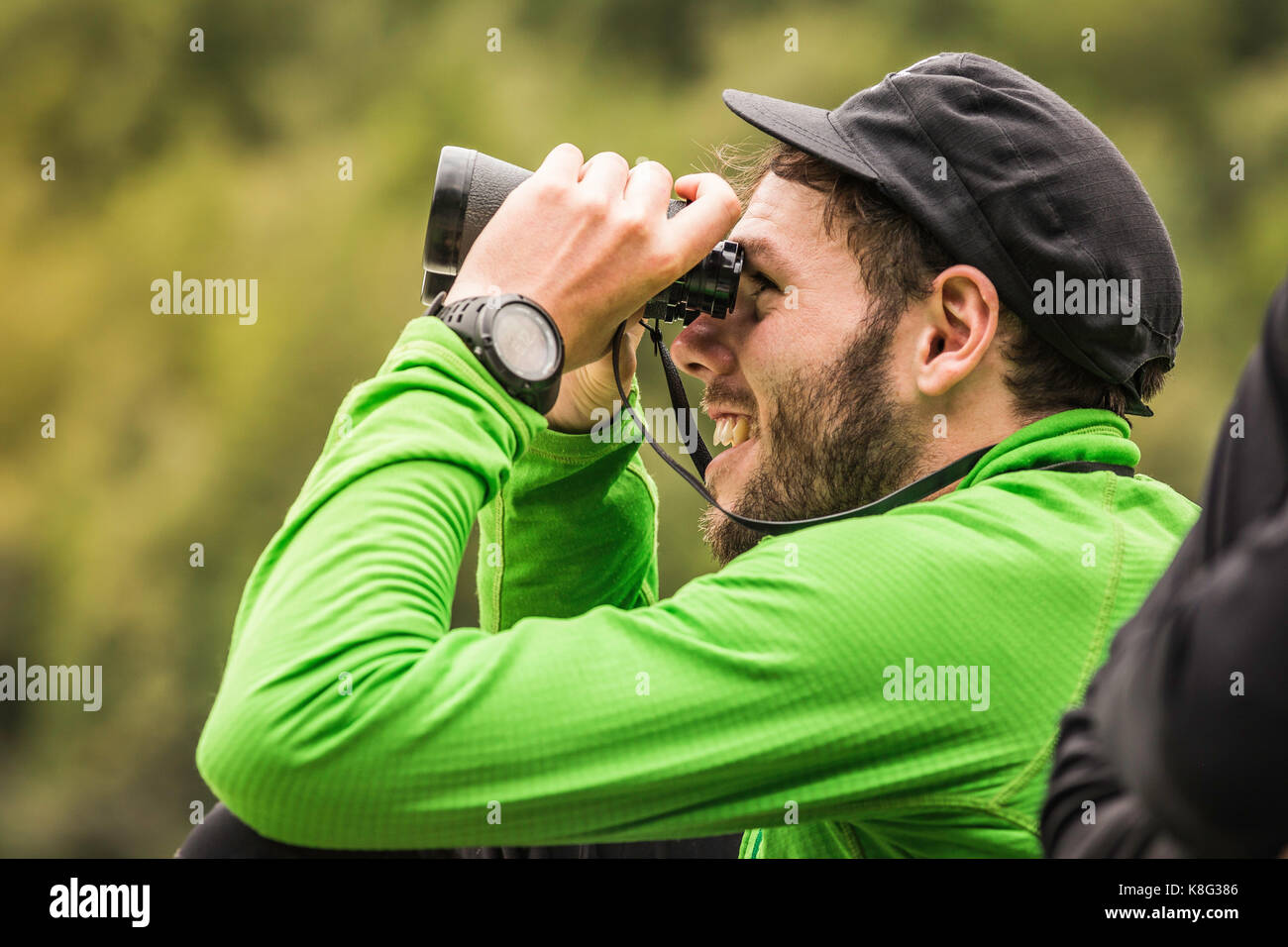 Young male backpacker looking through binoculars in Queulat National Park, Chile Stock Photo