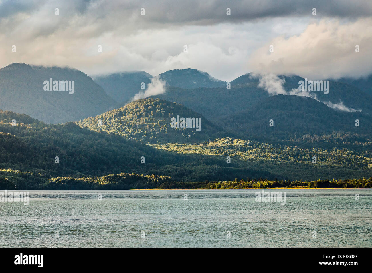 Mist rising from mountains over Lake Verde, Queulat National Park, Chile - Stock Image