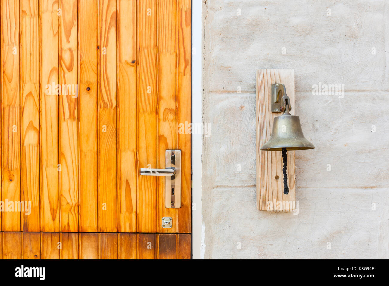 Brass bell attached outside next to house door for noise ringing communications notices or alarm rural camp farm Stock Photo