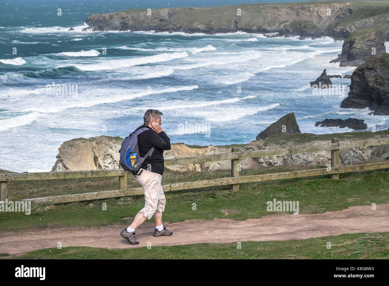 Bedruthan Steps - a female walker walking on the South West Coast Path at Bedruthan Steps on the North Cornwall - Stock Image