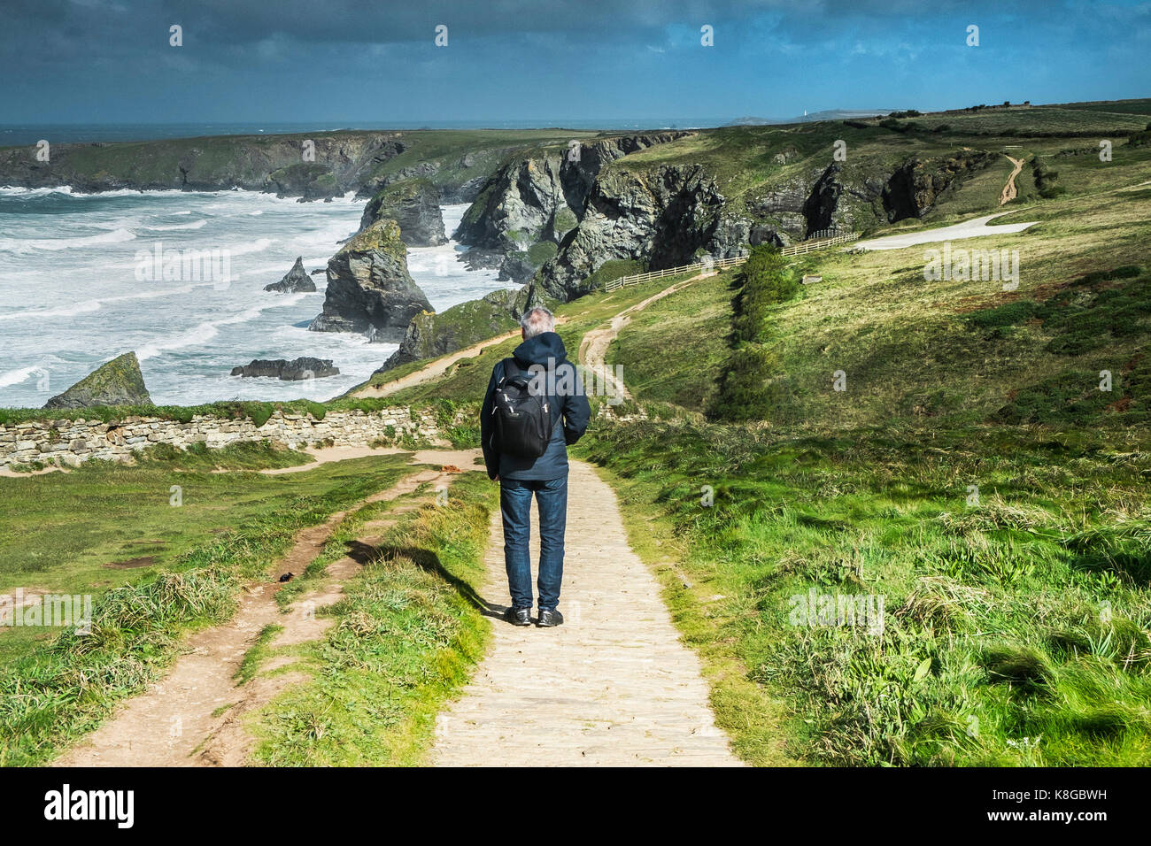 Bedruthan Steps - a tourist enjoying the view over Bedruthan Steps on the North Cornwall coast. - Stock Image