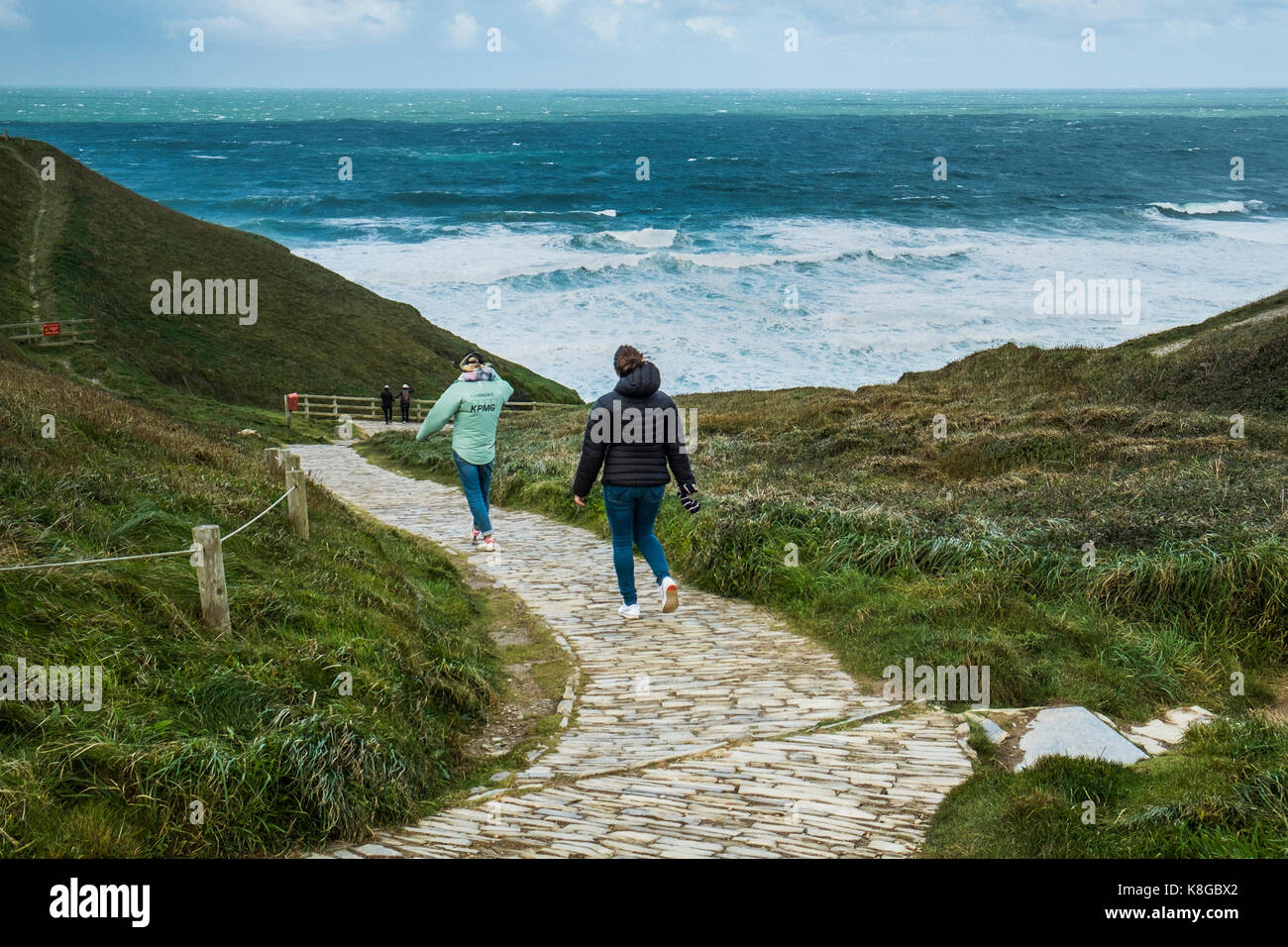 Bedruthan Steps - people walking down the coastal footpath at Bedruthan Steps on the North Cornwall coast. - Stock Image