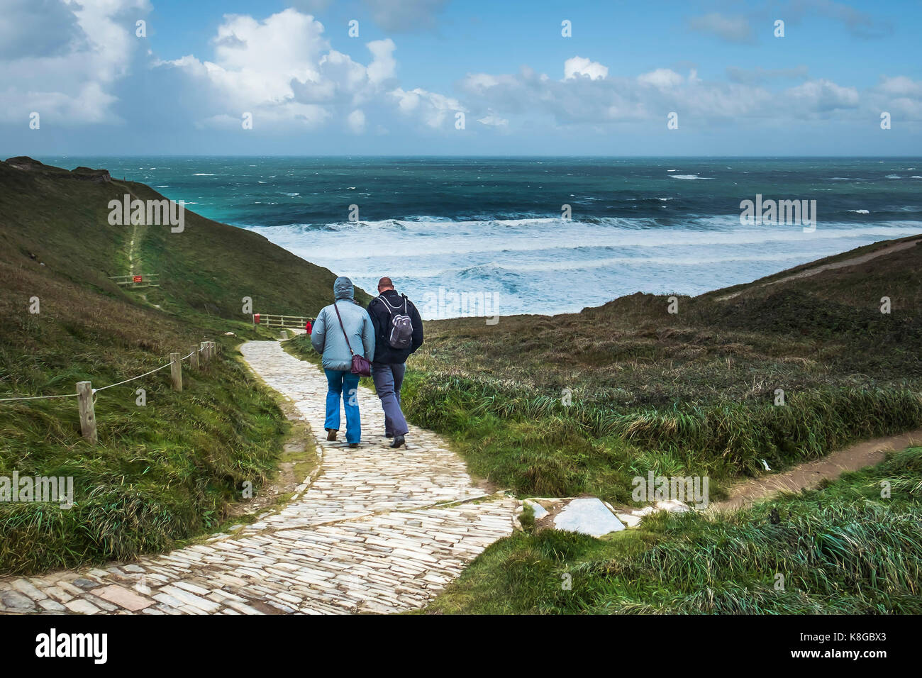 People walking down the coastal footpath at Bedruthan Steps on the North Cornwall coast. - Stock Image