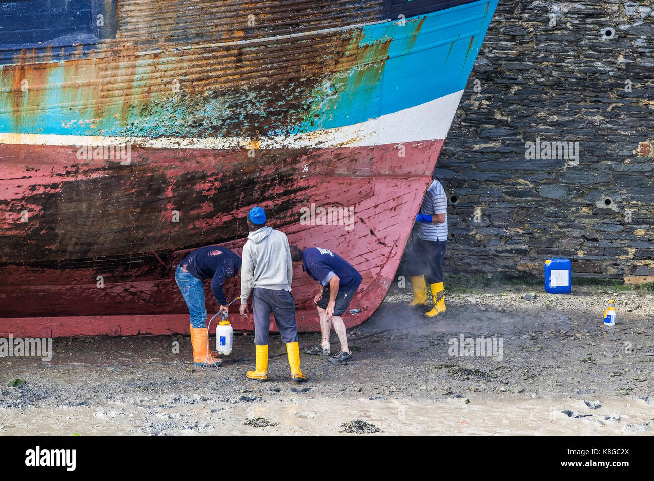 Fishing industry - workers inspecting the hull of a fishing trawler at low tide in Padstow Harbour on the North - Stock Image