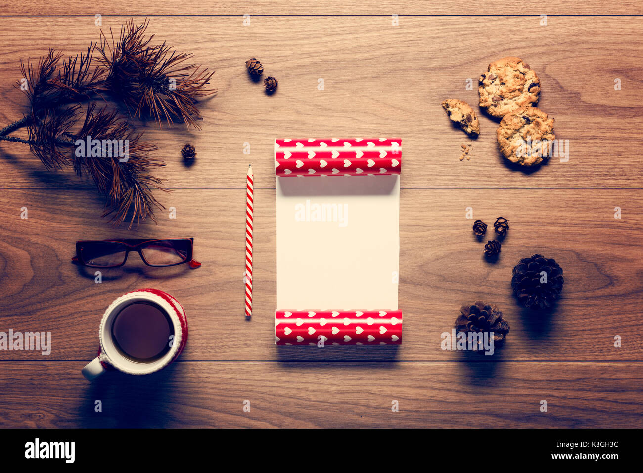 Magical christmas theme background, pine cones, coffee, cookies and an empty letter to santa on wooden table - Stock Image