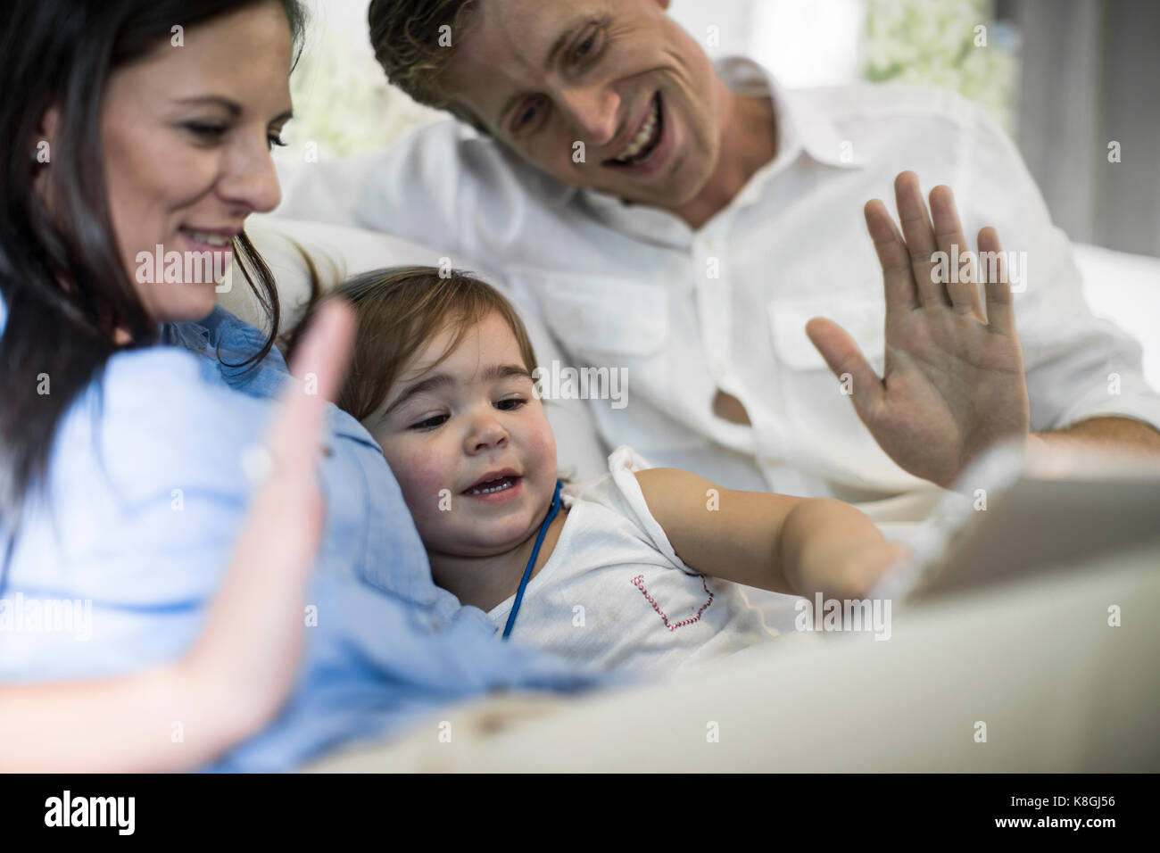 Husband and wife using digital tablet with baby girl on sofa - Stock Image