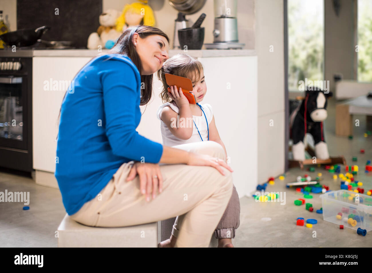 Mother listening in on baby girl's telephone call - Stock Image