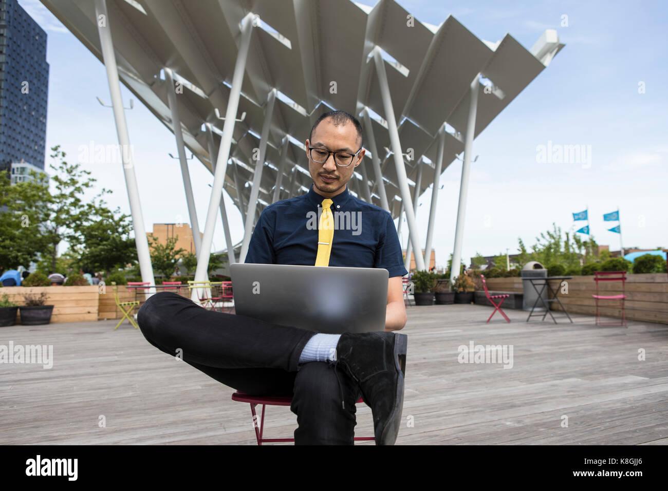 Businessman using laptop outside hotel, New York, USA - Stock Image