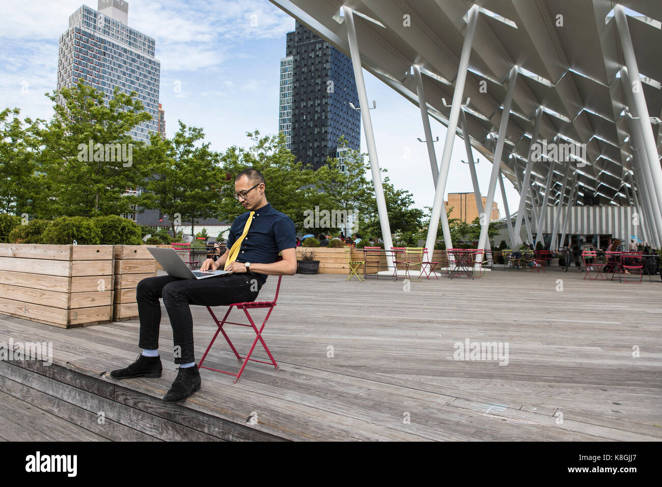Businessman typing on laptop outside hotel, New York, USA - Stock Image