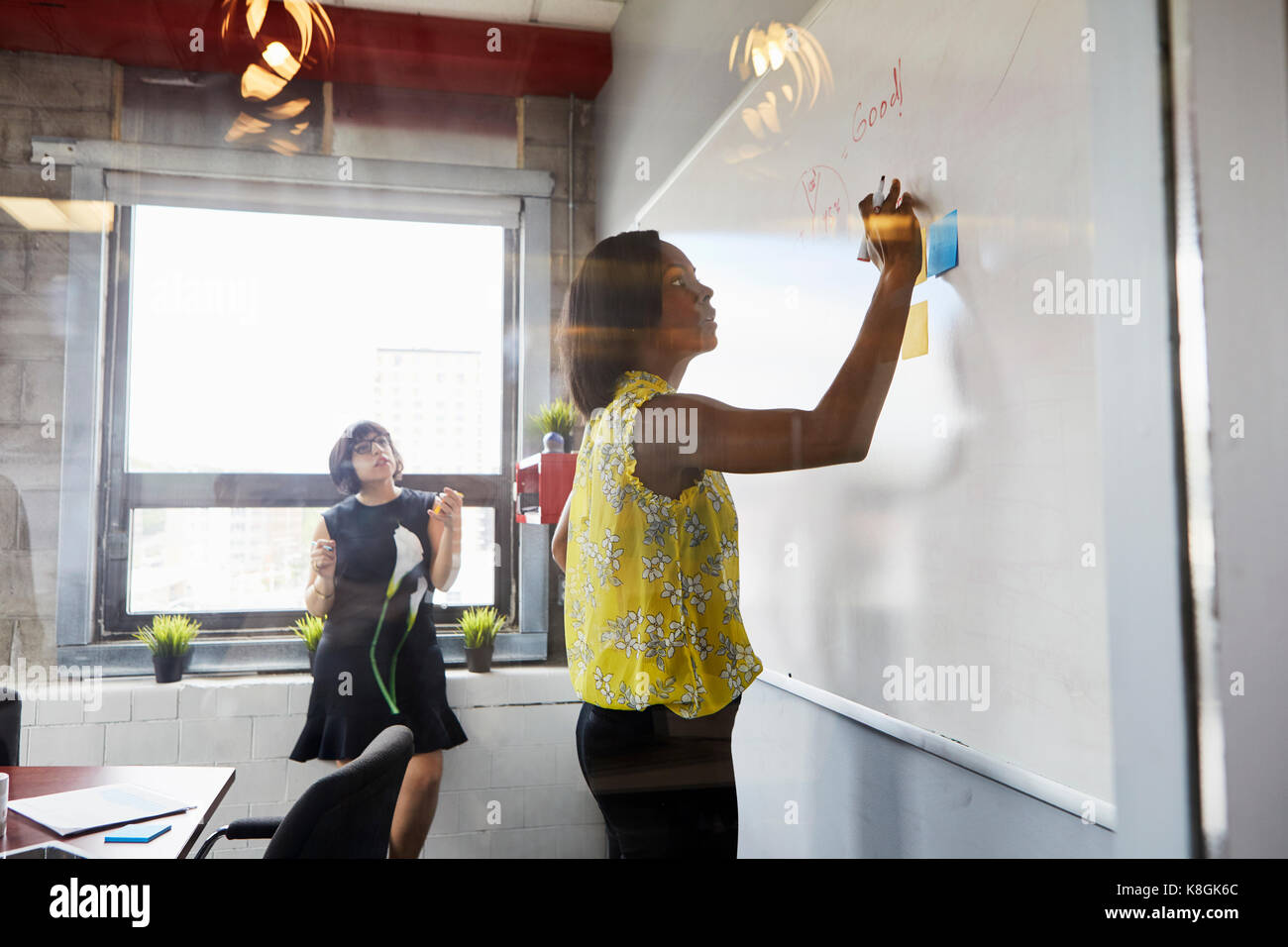Two women in office, solving problem, using whiteboard, sticky notes stuck on whiteboard Stock Photo
