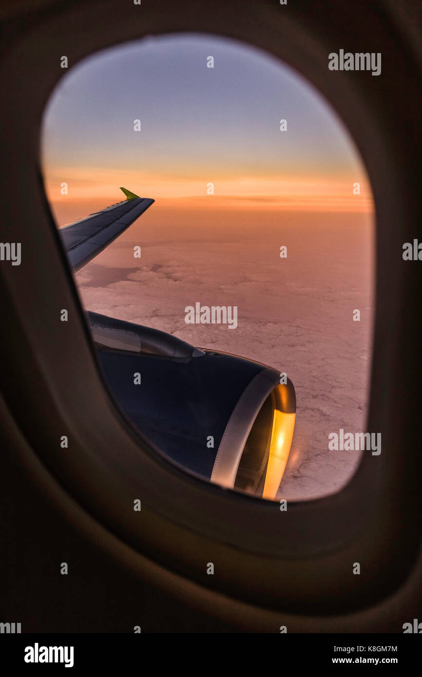 Sunset cloudscape and airplane wing through airplane window - Stock Image