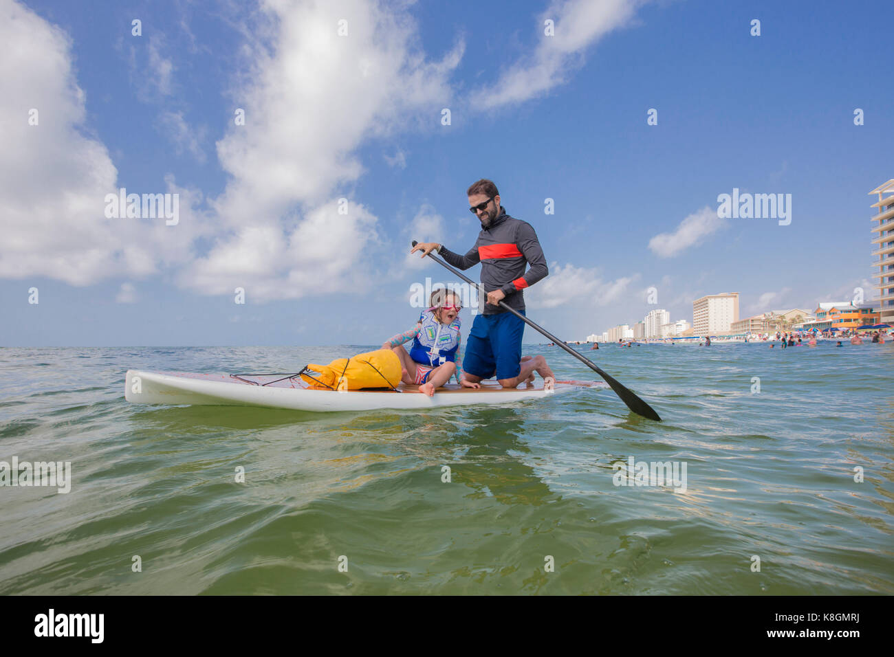 Father and daughter paddle boarding in the Gulf of Mexico, Florida, USA - Stock Image