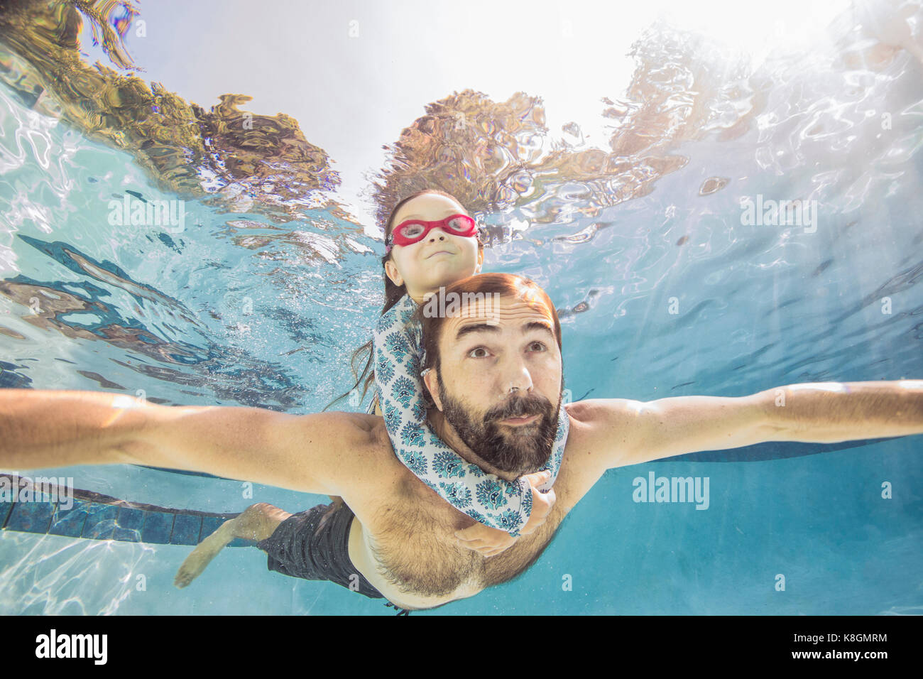 Underwater view of mature man swimming with daughter on piggy back - Stock Image