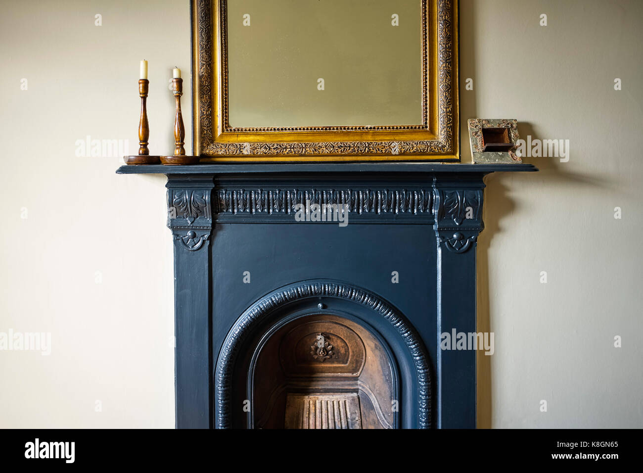 Bedroom cast iron fireplace with ornate French mirror above - Stock Image