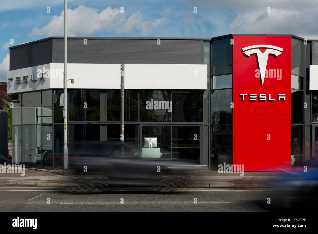 Traffic drives past a Tesla car showroom located in Heaton Chapel, though listed as South Manchester, in the UK - Stock Image