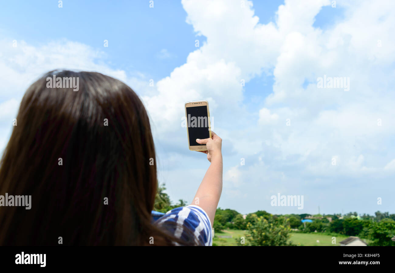 Picture of a girl clicking selfie. - Stock Image
