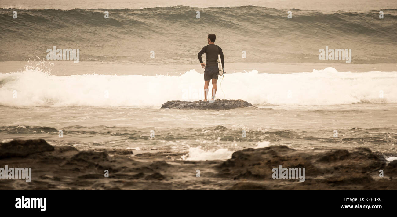 Rear view of surfer holding surfboard waiting for wave to break before heading out. - Stock Image