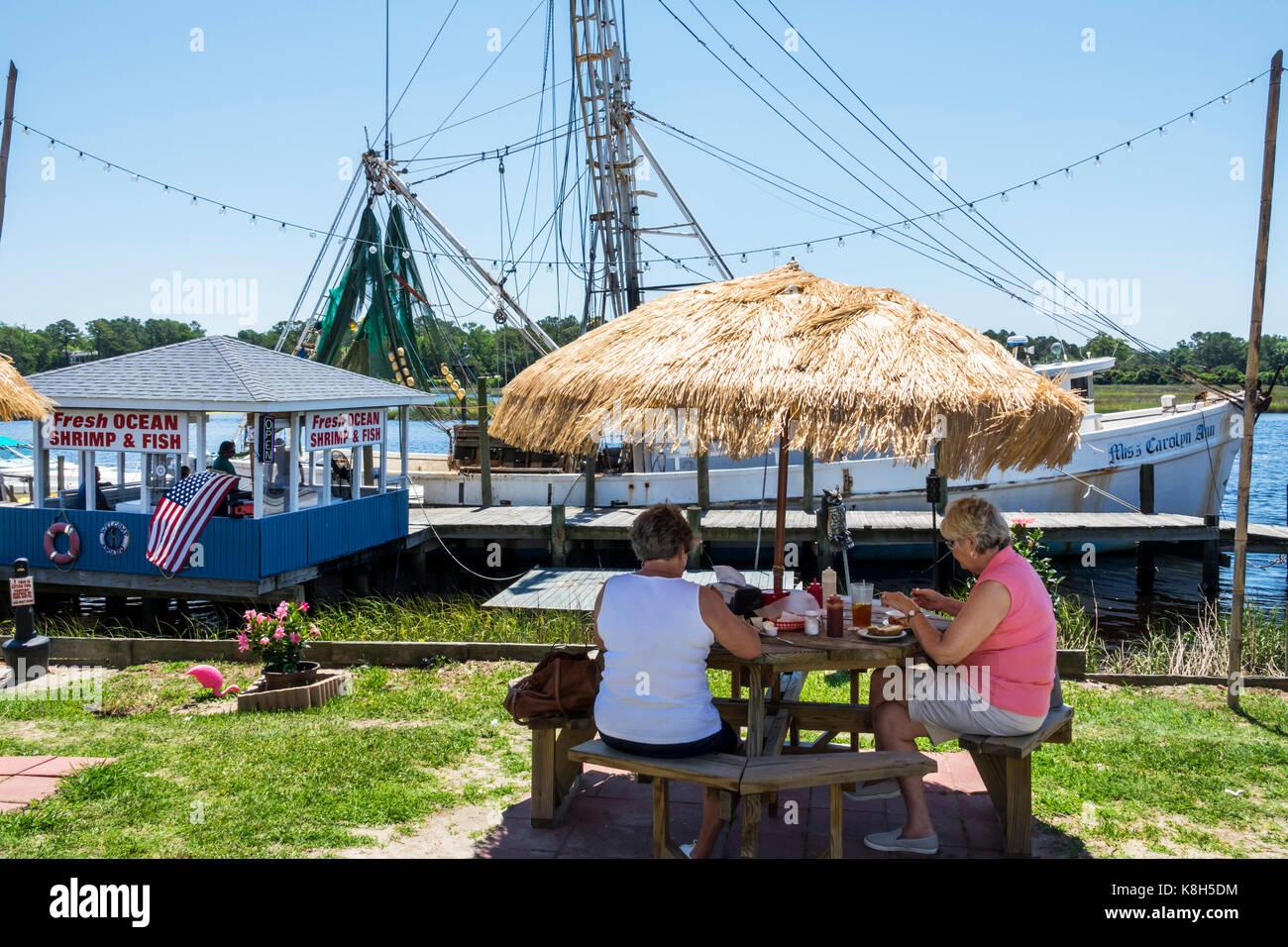 North Carolina NC Calabash fishing town seafood regional cuisine dining alfresco straw umbrella fishing boat dock - Stock Image