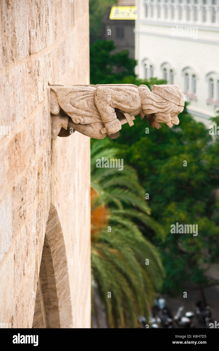Gargoyle Valencia Spain, a water spout in the form of a gargoyle clutching a crucifix sited on top of the medieval - Stock Image