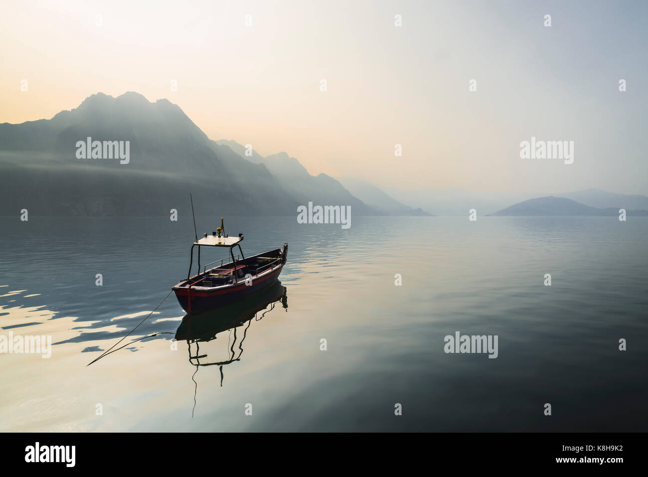 Panorama of a small boat on calm Lake Iseo in front of hazy mountains and Monte Isola in the morning sun, Lombardy, - Stock Image