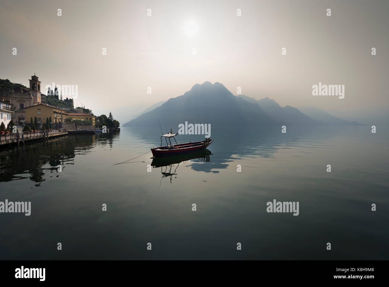 Panorama of a small boat on calm Lake Iseo in front of hazy mountains and Riva di Solto lakeside promenade in the - Stock Image