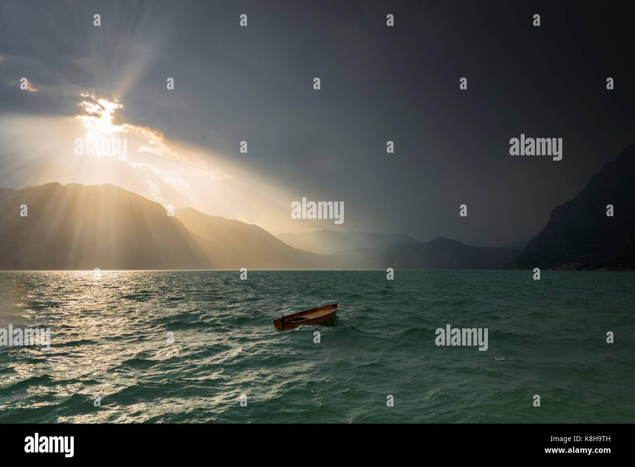 Thunderstorm raging on Lake Iseo with sun bursting through clouds and abandoned boat bopping up and down in the - Stock Image