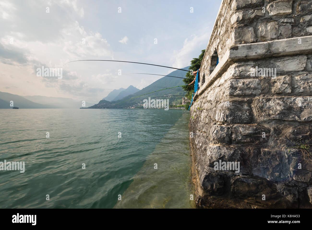 Angler mit langen Angelruten an der Mauer der Seepromenade von Sale Marasinao am Iseosee, Lombardei, Italien - Stock Image