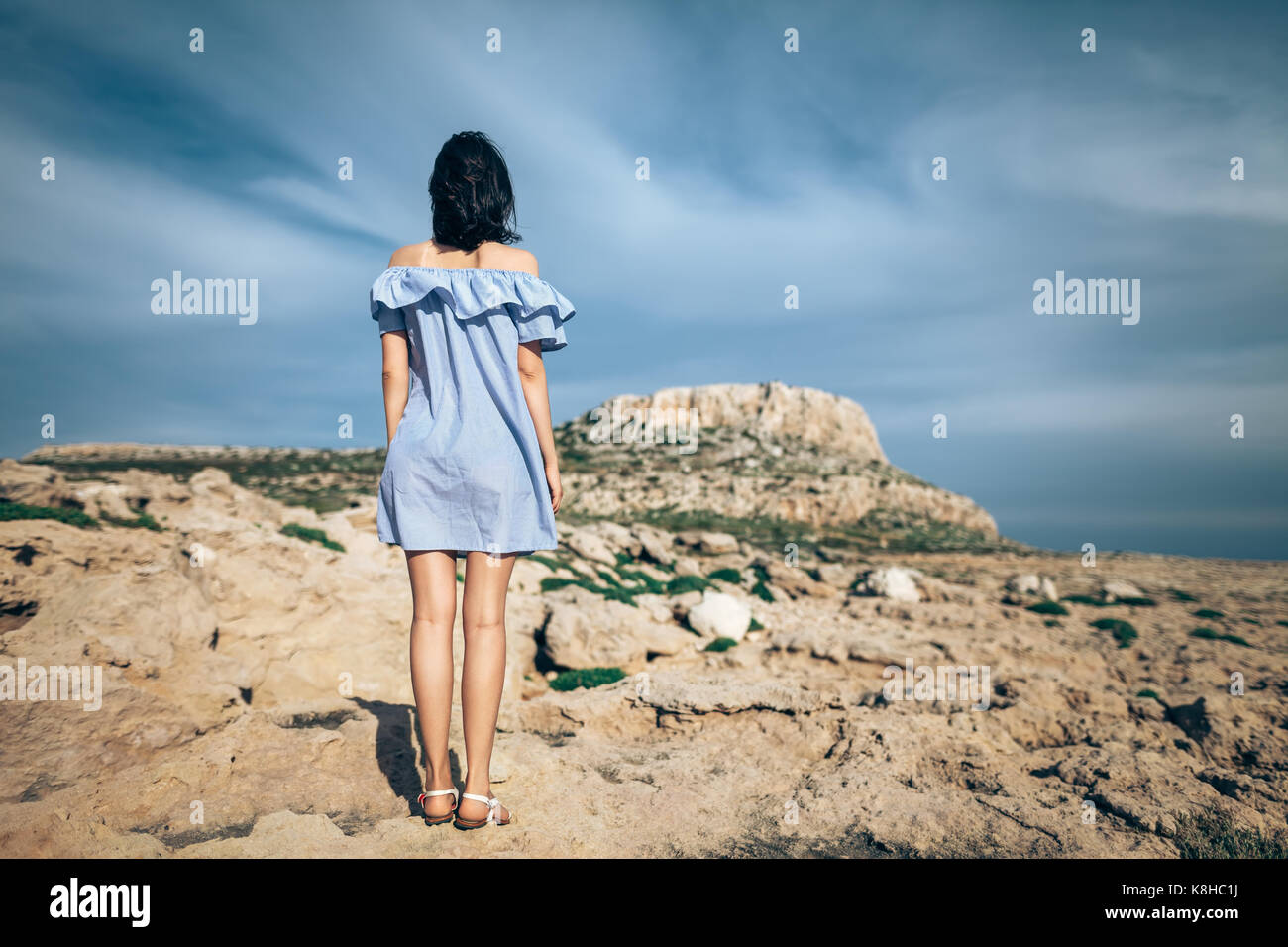 Back view of lonely woman standing on rocky desert with dramatic sky - Stock Image