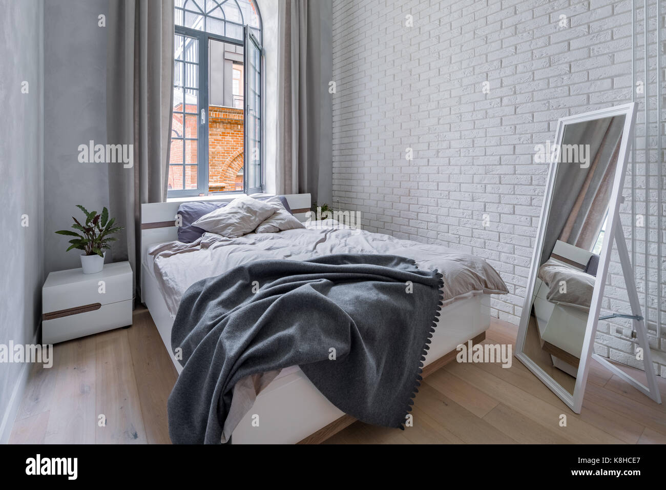 Loft Bedroom With White Brick Wall Double Bed And Mirror Stock