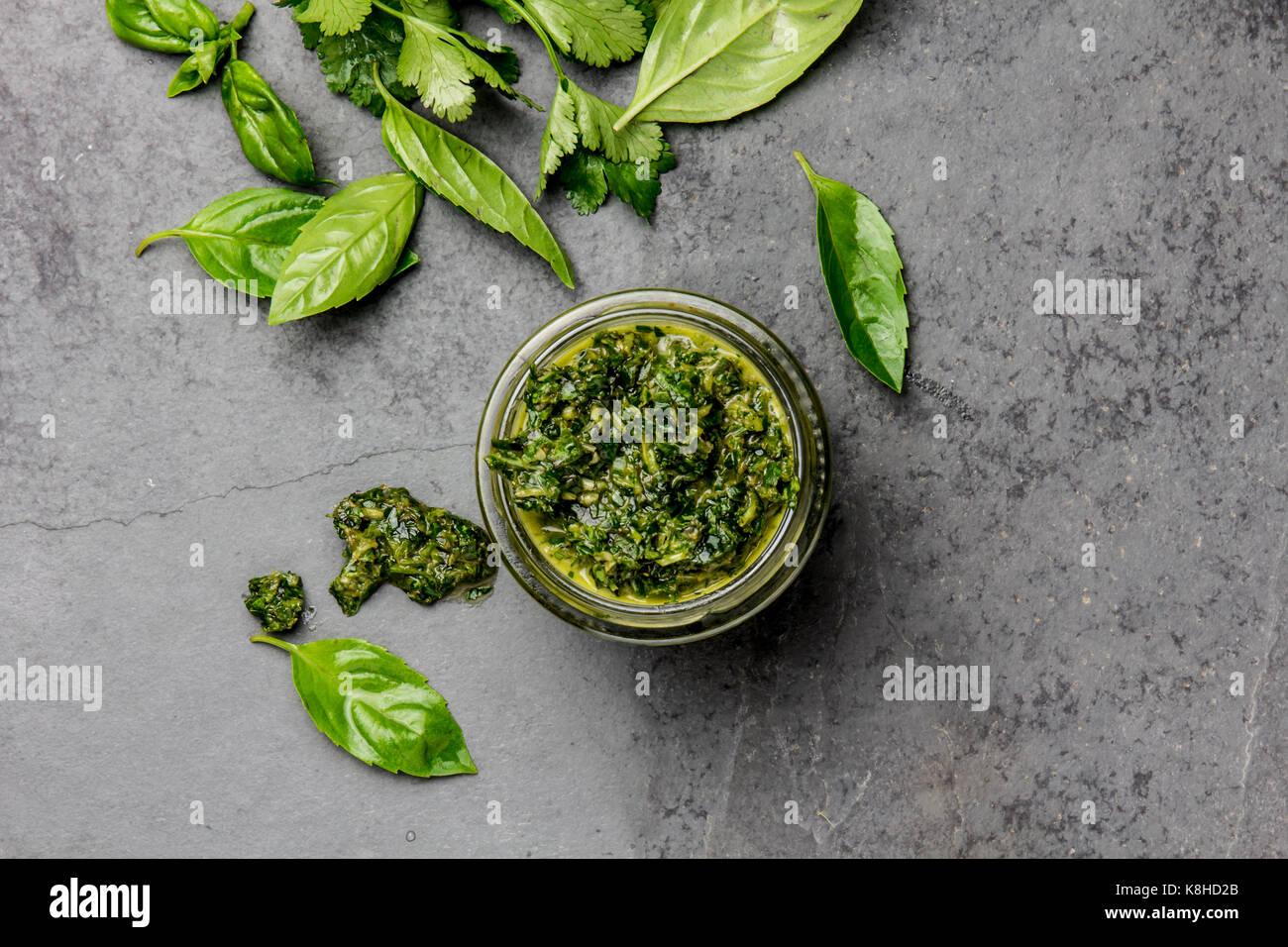 Chimichurri sauce. Argentine green parsley basil sauce chimichurri for barbecue asado in glass jar, gray slate background. Stock Photo