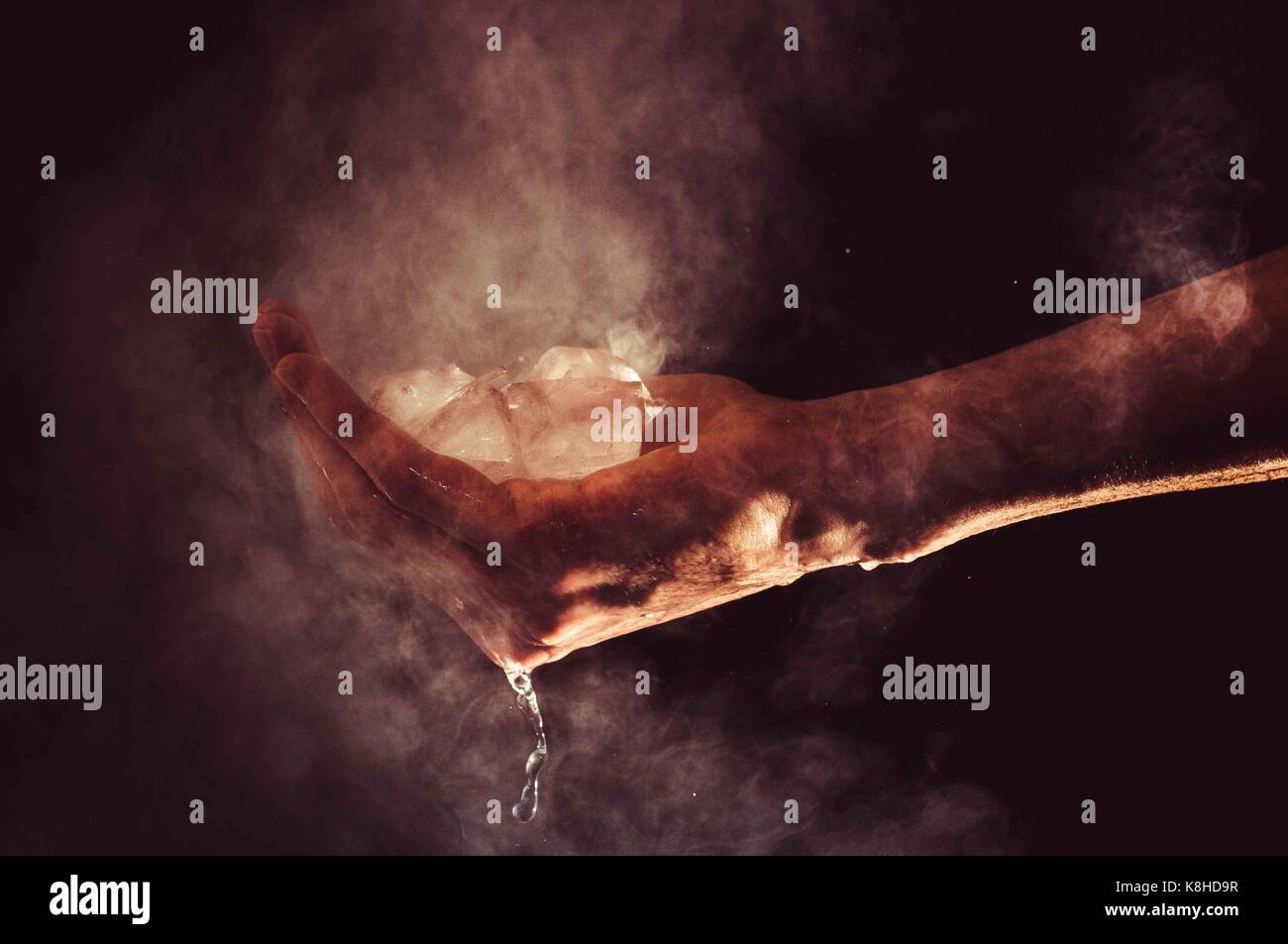 A hand is holding water in its three states: liquid, solid (ice), and gas (water vapor) - Stock Image