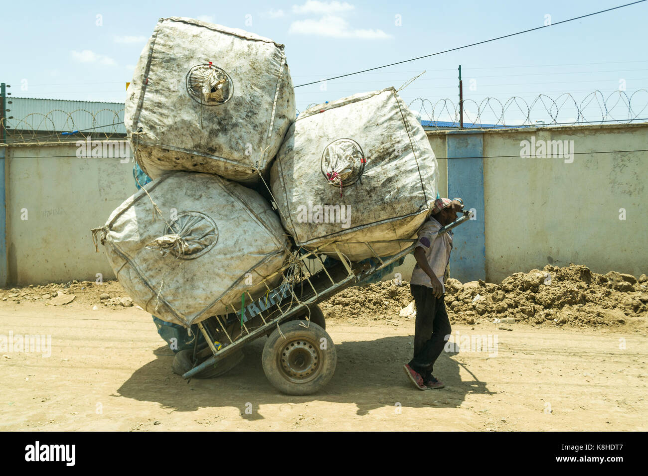 Hand cart puller stands resting in the shade of huge bags filled with plastic to recycle, Nairobi, Kenya - Stock Image