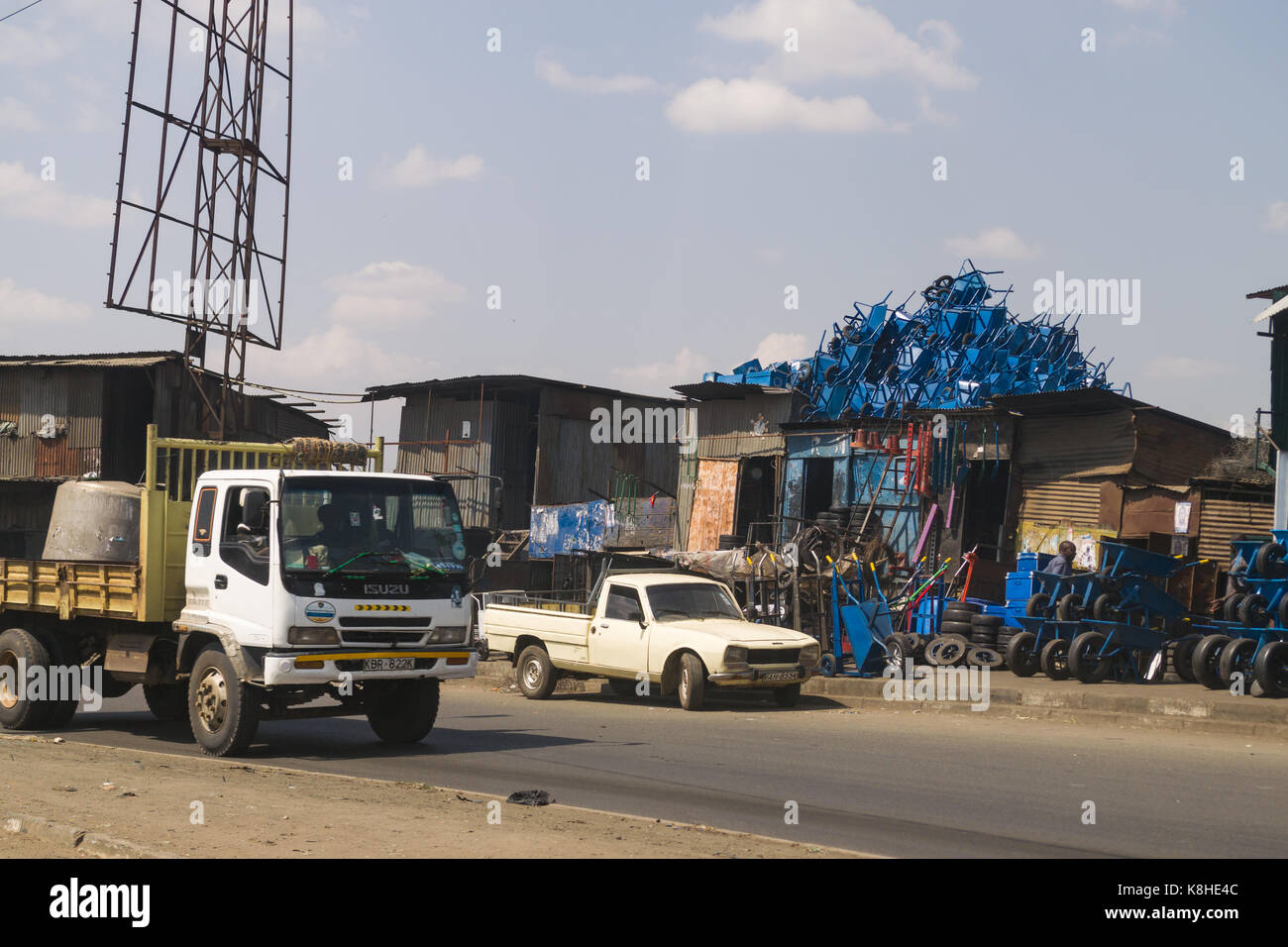 Roadside shop with wheelbarrows and other products for sale as vehicles drive past, Nairobi, Kenya - Stock Image