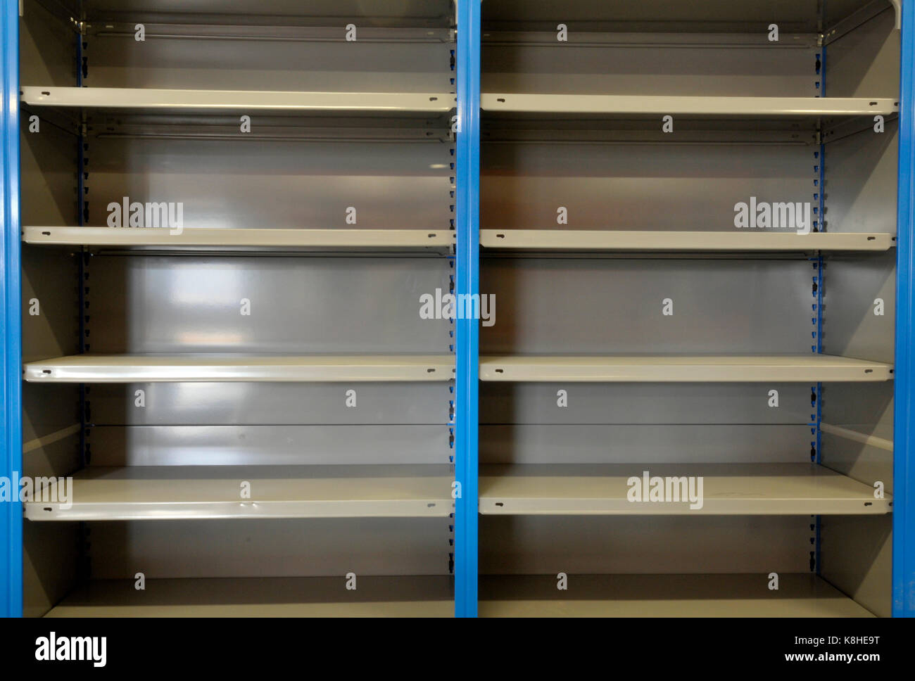 an empty industrial wooden and metal stacking shelving system of shelves at a large industrial warehousing facility - Stock Image