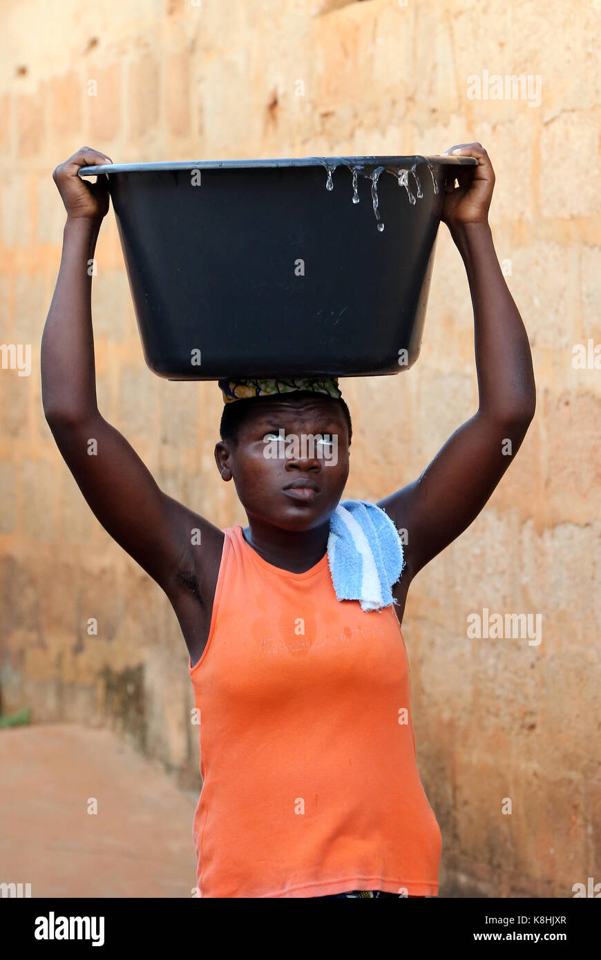 African village life. water chore. african girl carrying a basin of water on head. togoville. togo. - Stock Image