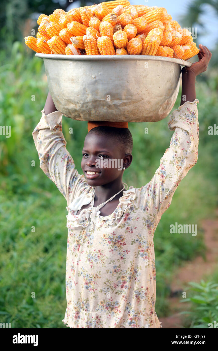 Girl carrying platter with corn on head. togo. Stock Photo