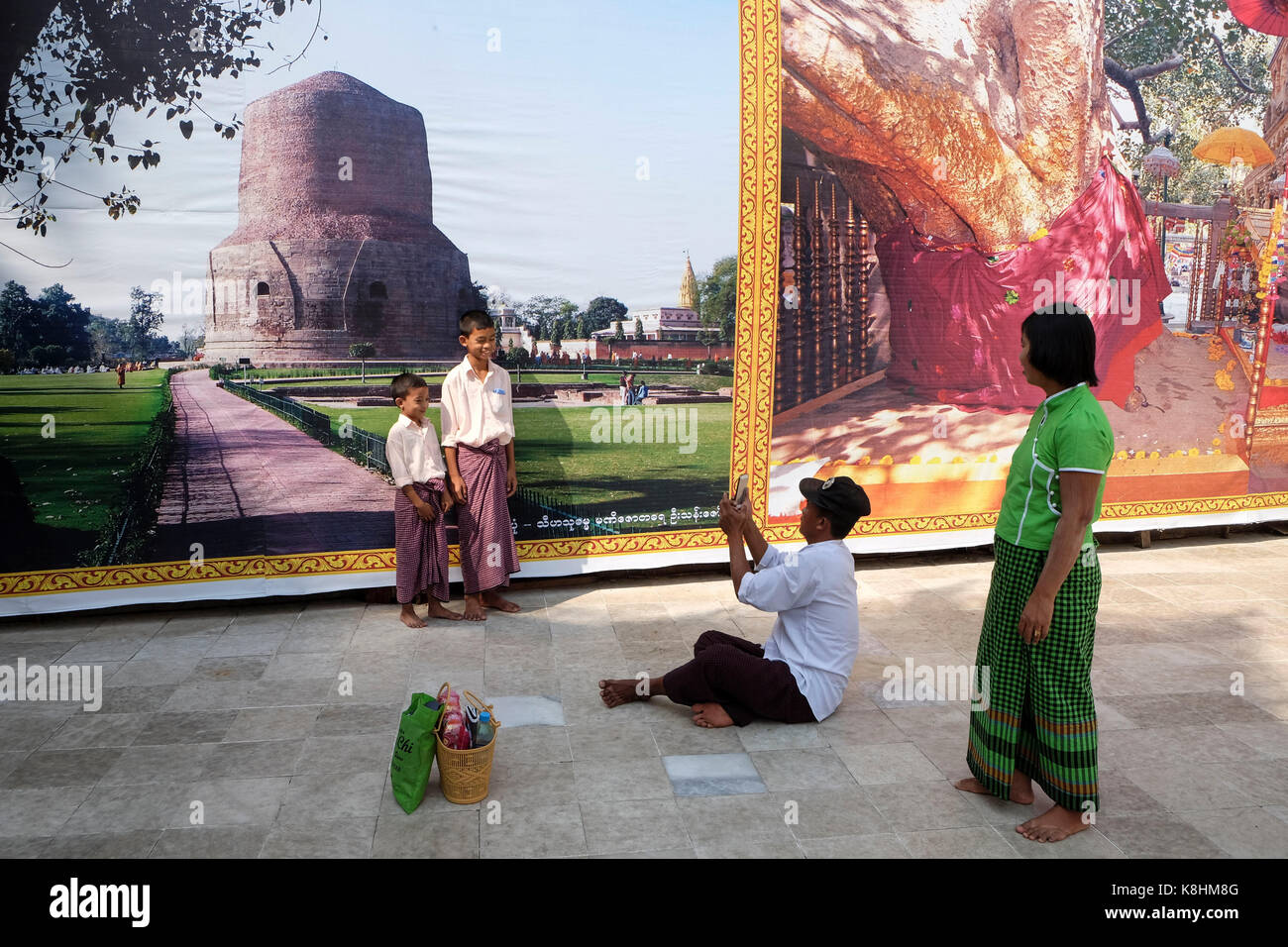 Burma, Myanmar: Burmese tourists taking pictures of each other in front of giant posters in Rangoon. Stock Photo
