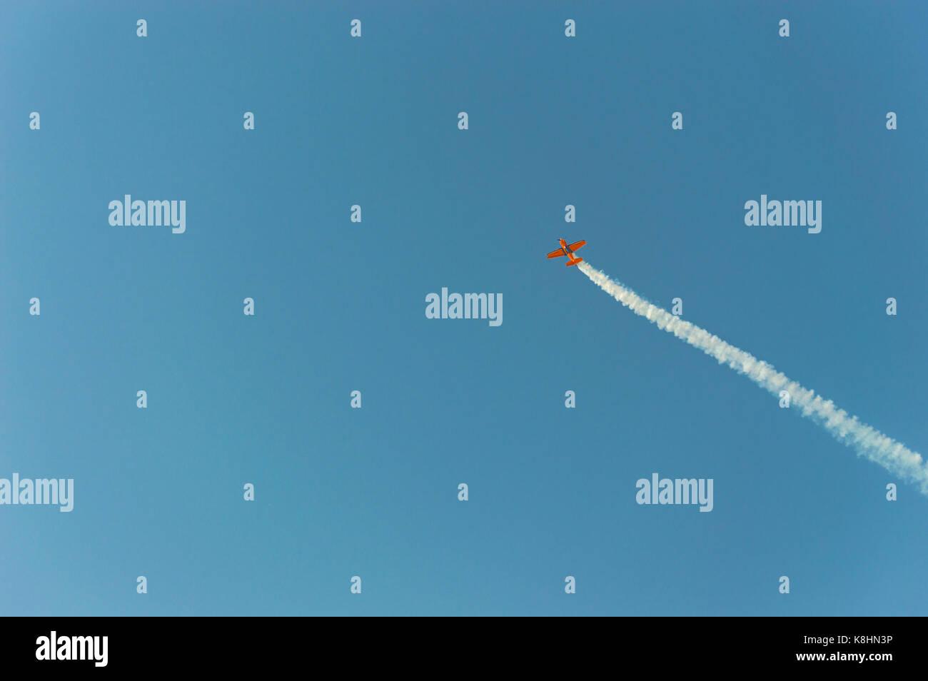 Aerobatic plane  leaving a white smoke trail in the bright blue sky. - Stock Image