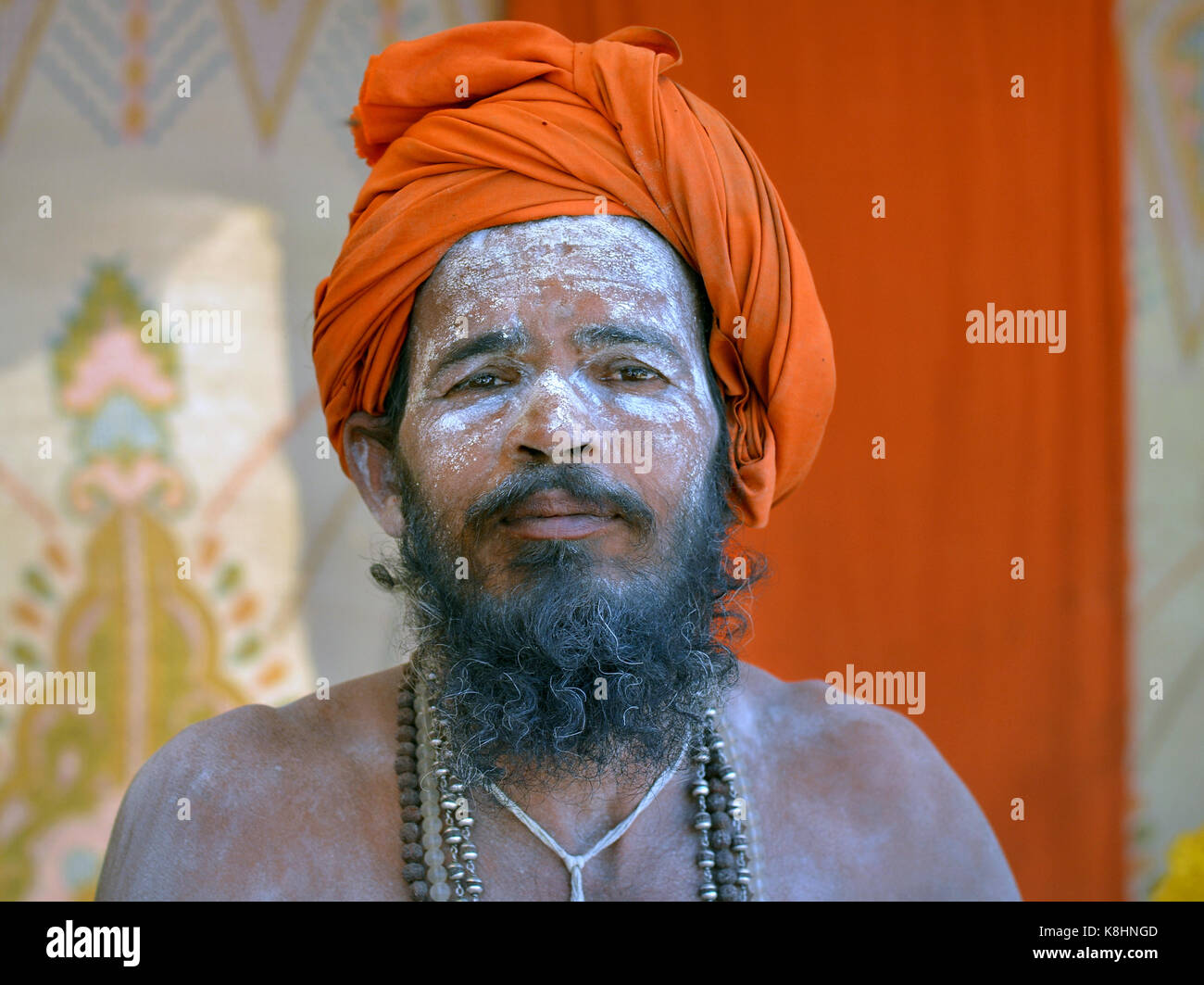 Young Indian Hindu sadhu with orange turban and sacred white ash (vibhuti) all over his face and beard - Stock Image