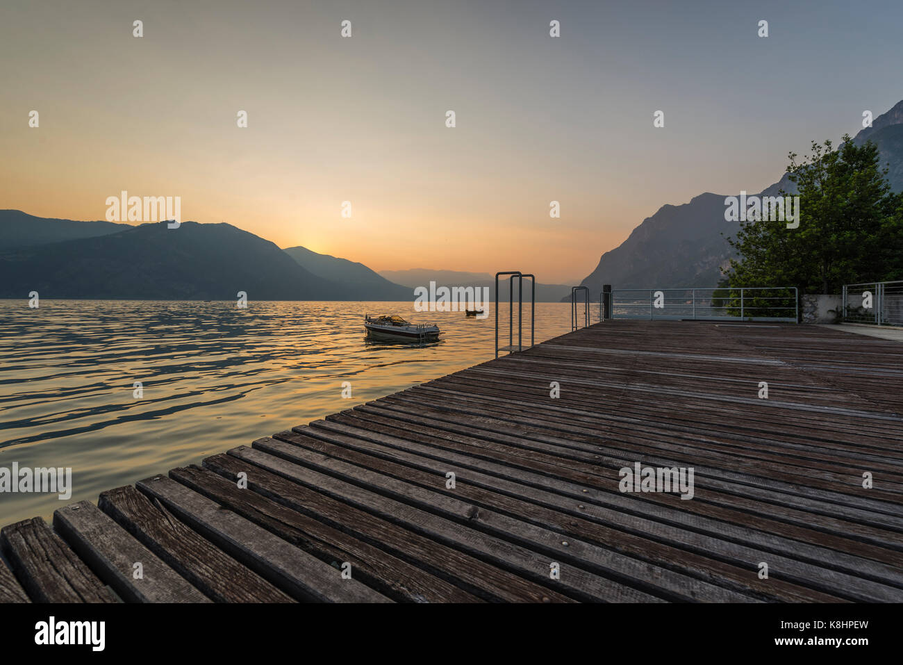 Jetty with wooden timber planks and boat ont he lake in the sunset over Lake Iseo and surrounding mountains, Lombary, - Stock Image