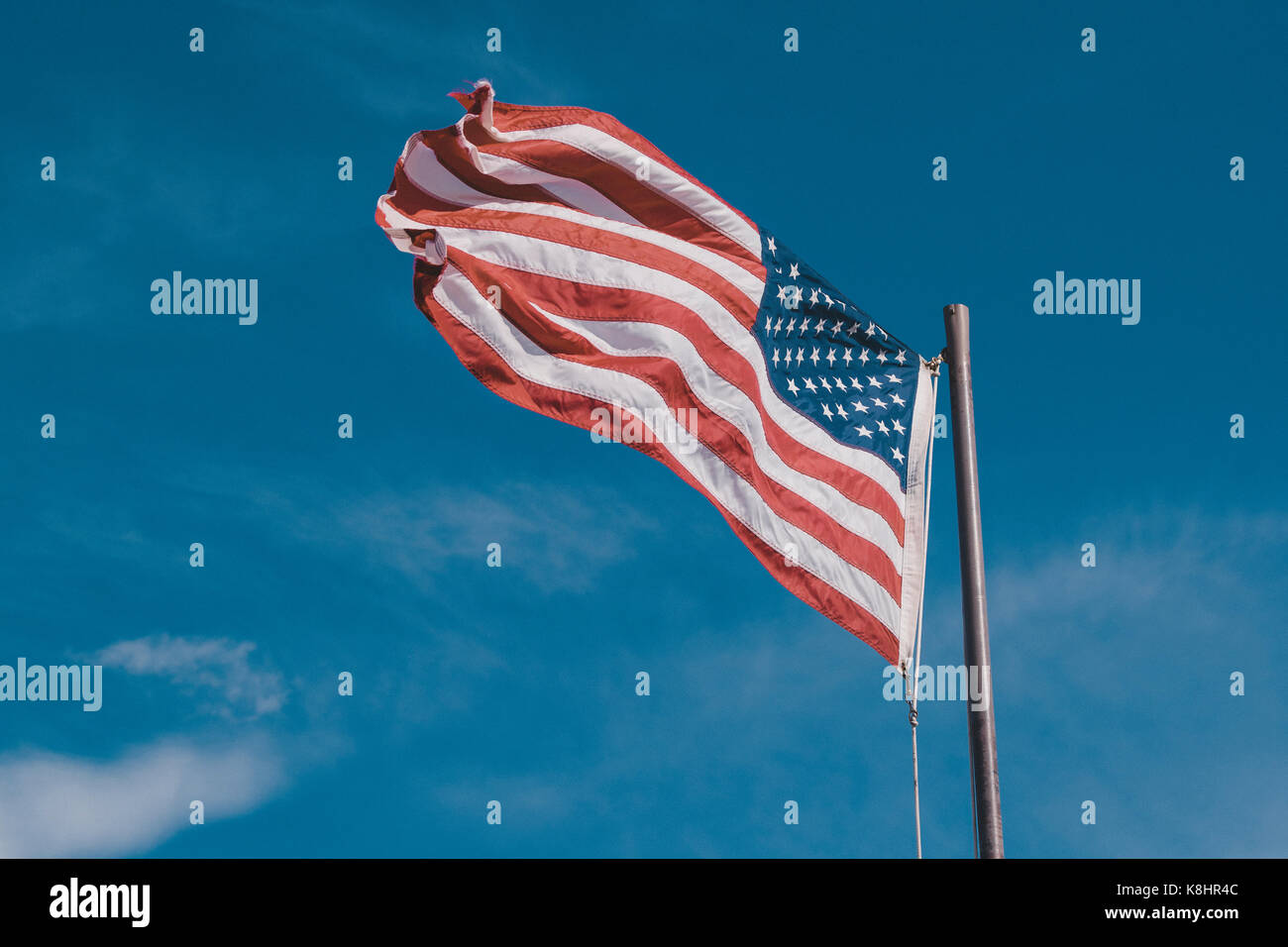 Low angle view of American Flag against blue sky Stock Photo