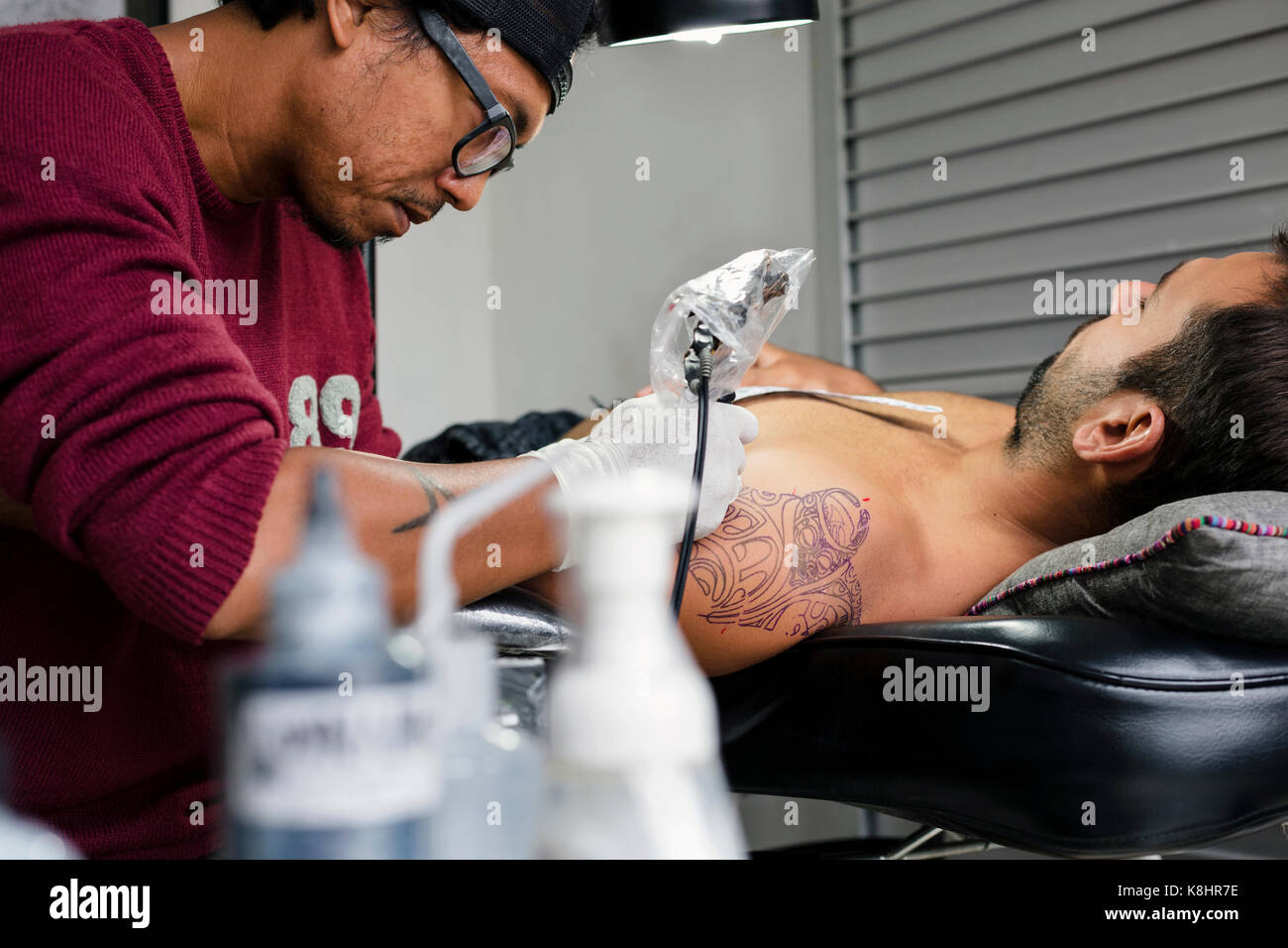 Tattoo artist tattooing man's shoulder - Stock Image