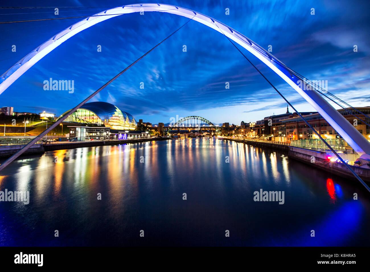 Illuminated Gateshead Millennium Bridge over river against sky Stock Photo