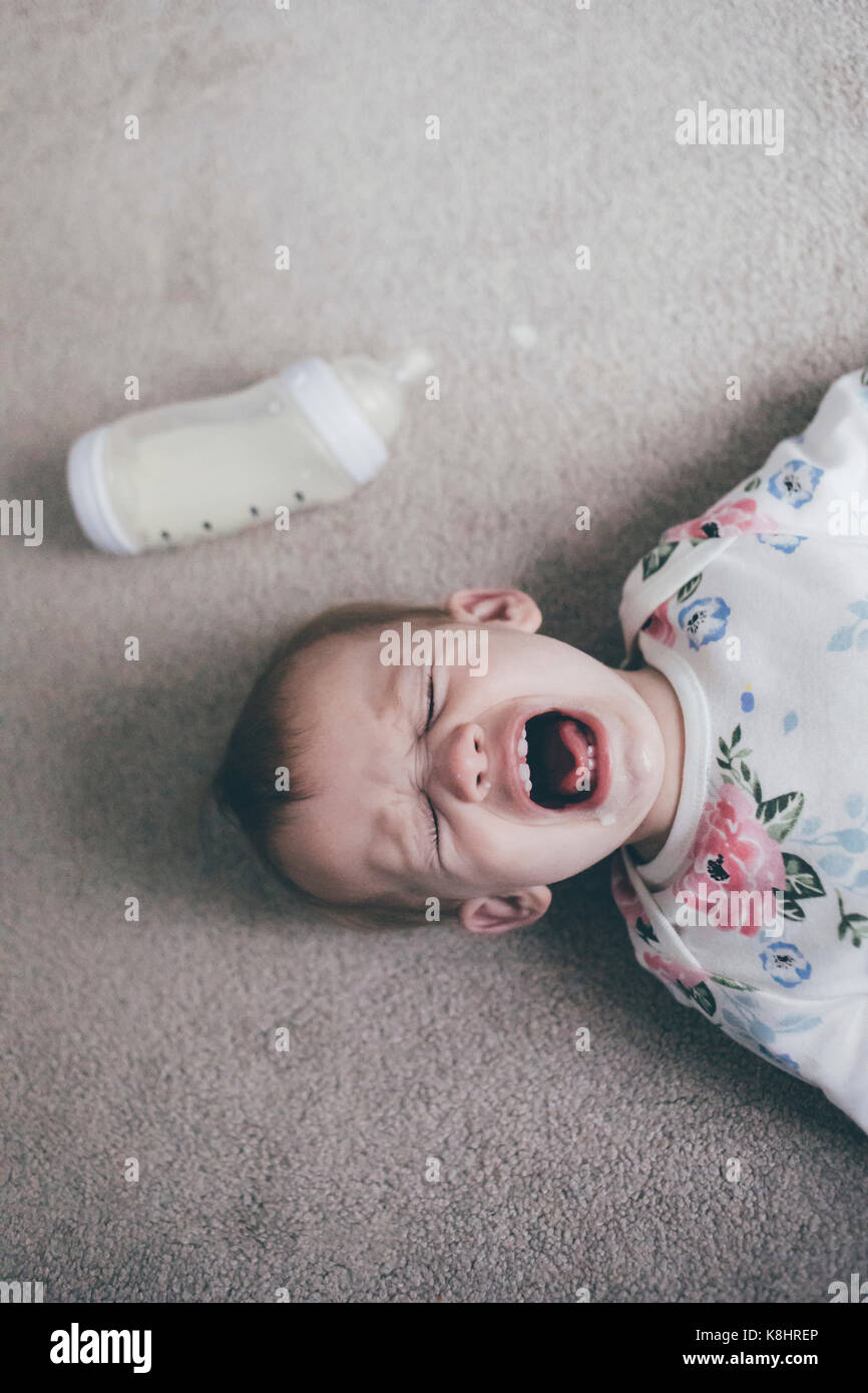 Overhead view of toddler crying while lying on floor at home - Stock Image